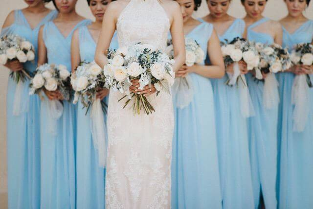 Bride wearing lacey dress in front of bridesmaids wearing light blue dresses all carrying a bouquet each