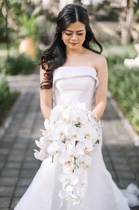 Bride holding white orchid flower bouquet