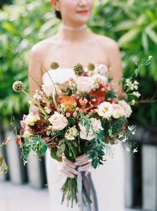 Bride holding a colourful flower bouquet