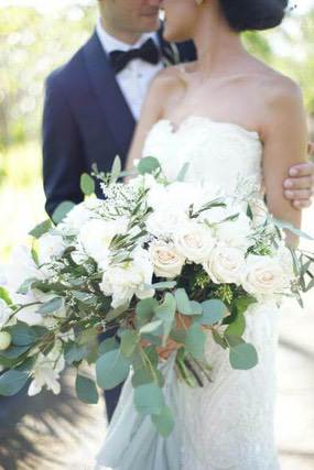 Groom cuddling Bride who is holding white rose bouquet