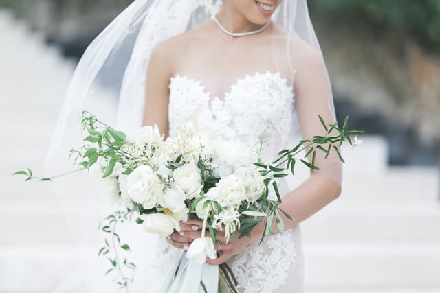 Bride wearing wedding dress and veil carrying white rose bouquet