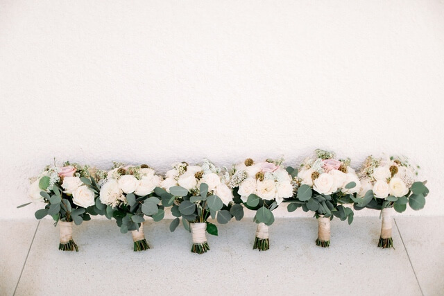 Six hand bouquets lined up against the wall