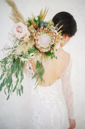 Bride carrying oversized bouquet on her shoulder