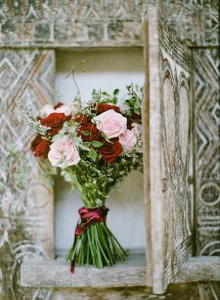 Red and pink flower bouquet posed in wooden frame