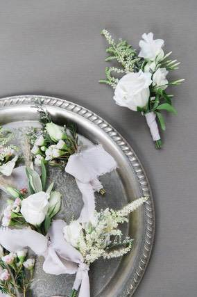 One white flower boutonniere next to a round silver tray with more boutonnieres
