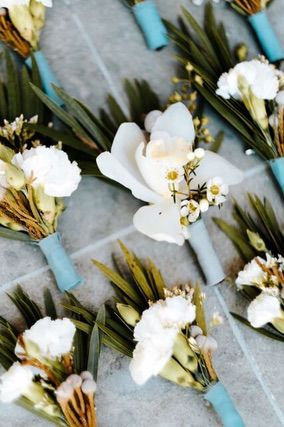 Several white flower boutonnieres with soft blue binding