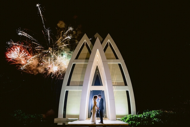 Bride and Groom standing in front of chapel with fireworks in sky