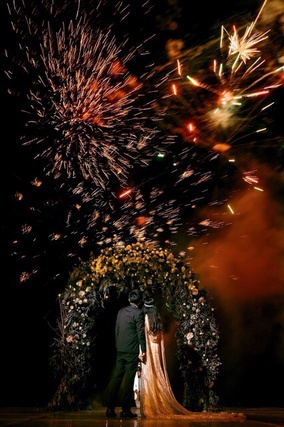 Bride and Groom under flower arch watching fireworks display