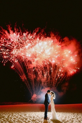 Bride and Groom kissing on beach with red fireworks in background