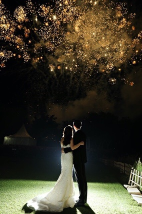 Bride and Groom hugging in garden with gold fireworks above