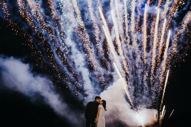 Bride and Groom kissing during fireworks display