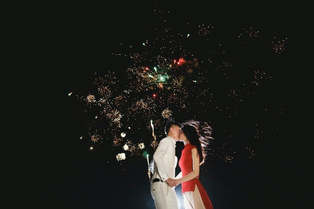 Bride and Groom kissing with fireworks display behind