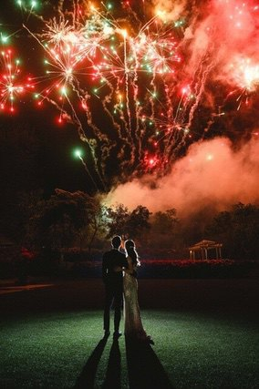 Bride and Groom watching red and green fireworks display