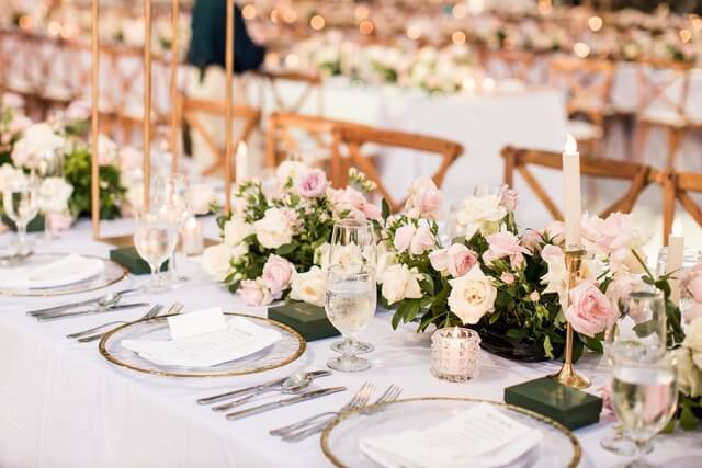 Plates, cutlery, drinking glasses and small flower centerpieces on long tables