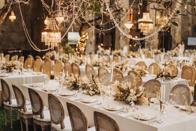 Long tables set for dinner with wicker chairs and hanging fairy lights and chandeliers