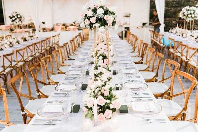 Long table with flower centerpieces and wooden chairs
