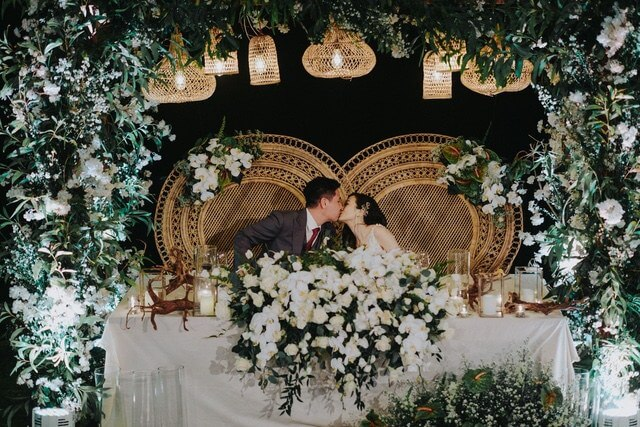 Bride and Groom kissing seated in separate large wicker chairs surrounded by white and green flowers