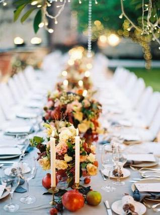 Candles and autumnnal coloured fruits and flowers spanning in the length of a long table