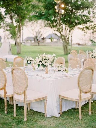 Square white table set for dinner with wicker chairs