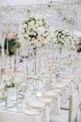 Lolipop shaped flower centerpieces on long white tables