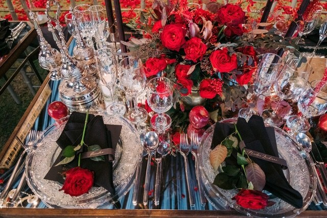 Glass plates, silver cutlery, red rose centerpieces on mirror table