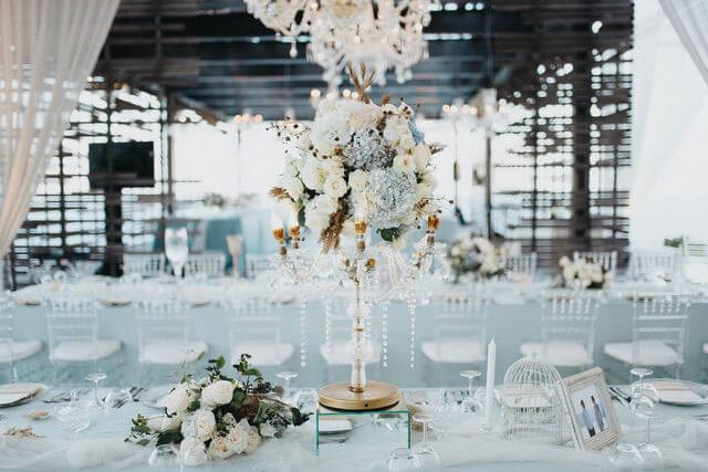 Tall flower centerpiece on long table with light blue and grey linen