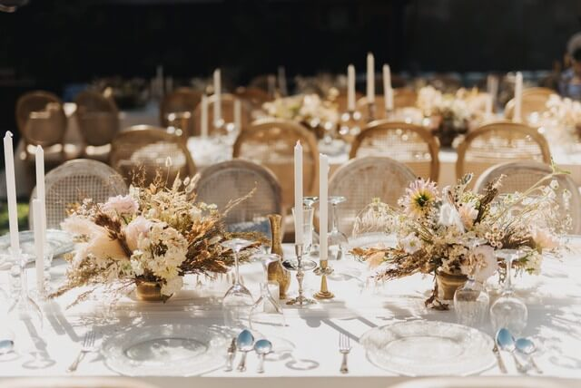 Dried flower centerpieces with candles and cuttlery on table