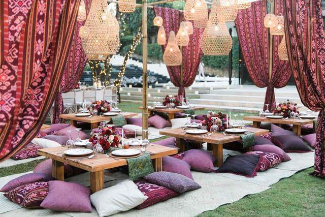 Low square wooden table with pillow seats under batik drapes and wicker hanging lanterns
