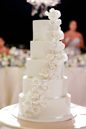 Five tiered white wedding cake with white flower decoration