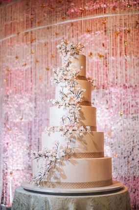 Five tiered white wedding cake with pink backdrop