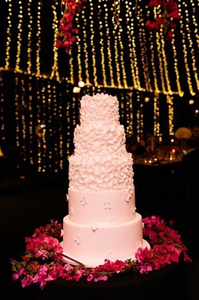 Five tiered white wedding cake on a bed of red roses in front of fairy lights