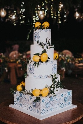 Five tiered wedding cake with blue motif and lemons place around tiers