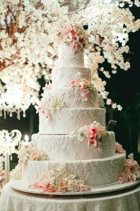 Six tiered wedding cake with pink and white flower accessories