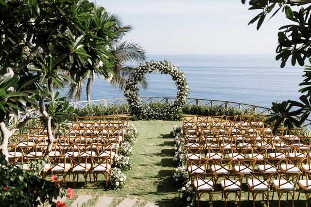 Large ceremonial round flower arch in front of rows of wooden chairs overlooking the ocean