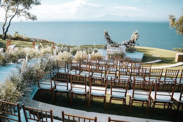 Wedding ceremony with wooden chairs on grass amphiteathre with ocean backdrop