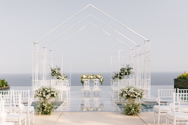Church shaped metal framework with white chairs and flowers inside
