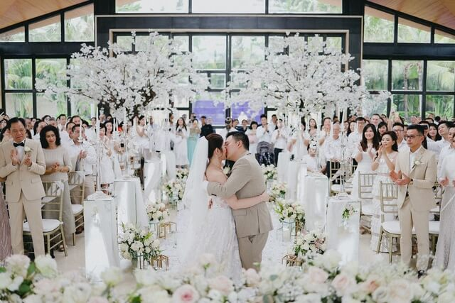 Bride and Groom kissing with guests clapping surrounded by flower and white trees
