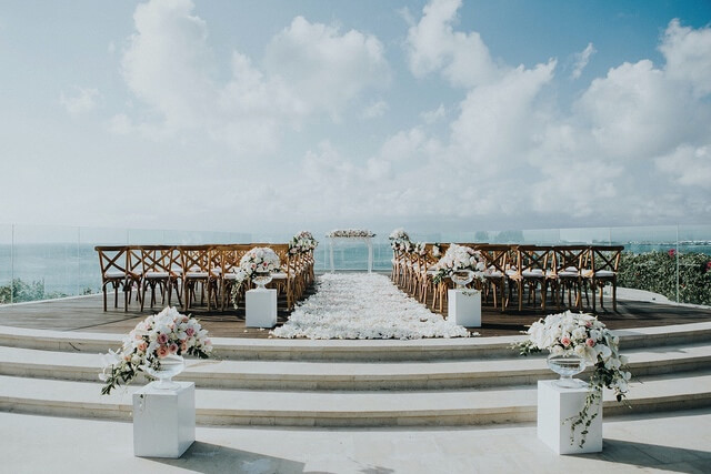 Wedding ceremony with rows of wooden chairs separated by white flower petal carpet