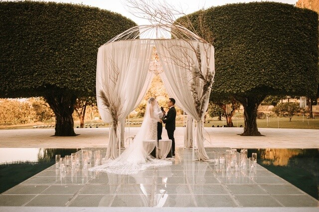 Bride and Groom taking vows inside white pergola with white drapes on floating stage