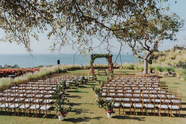 Large garden with lots of rows of wooden chairs facing ocean