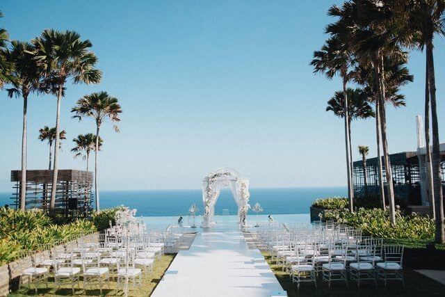 White wedding ceremony pergola in front of rows of acrylic chairs