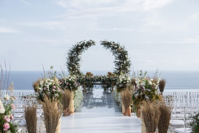 Wedding ceremony flower arch with ocean backdrop