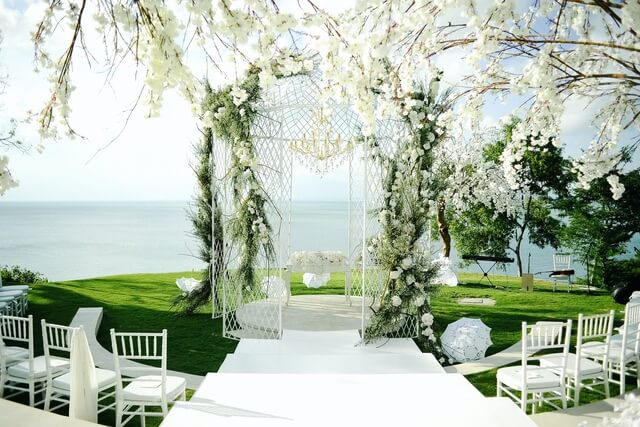White iron pergola on grass stage with white chairs and white trees