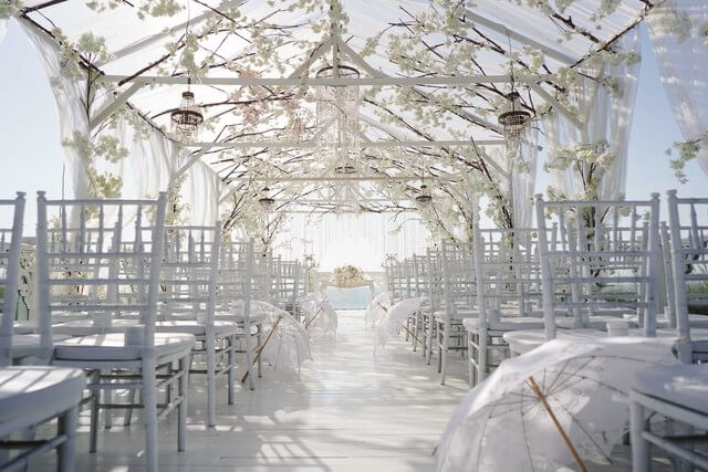 White flower canopy above white chairs and white umbrellas