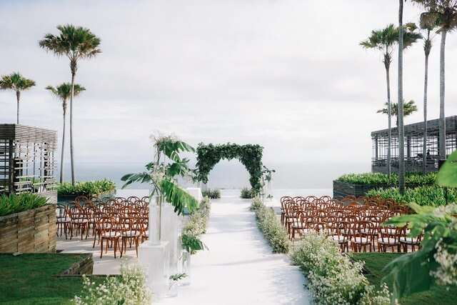 Green square wedding arch with rows of wooden chairs and green plants