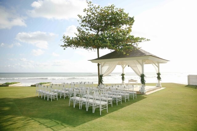 White wooden gazebo with rows of white chairs in garden on the oceanfront