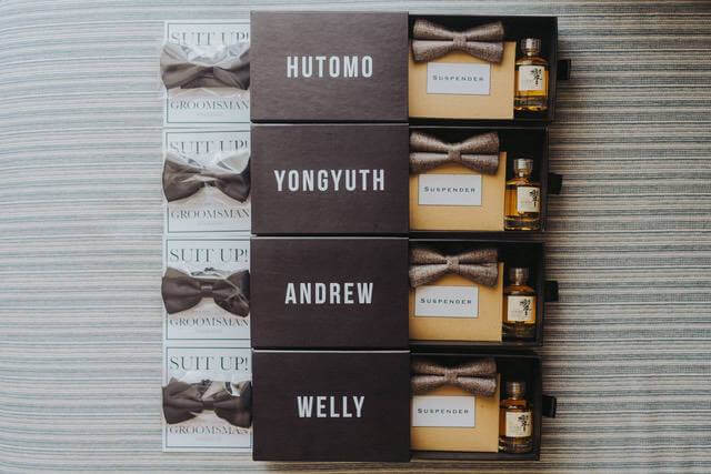 Four boxes with a man's name on each box each containing a bow tie and a small bottle of whiskey