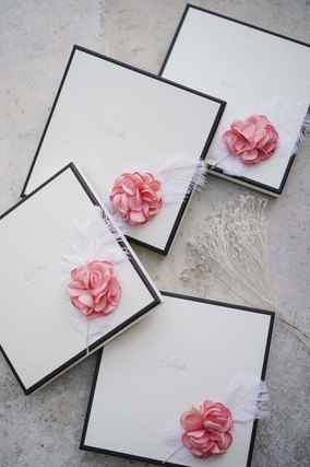 Four square boxes with white front and a pink flower attached to each