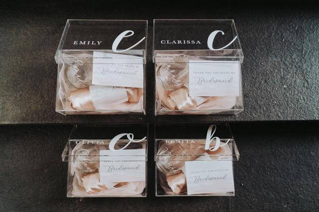 Four acrylic boxes with woman's name on each box containing peach linen items