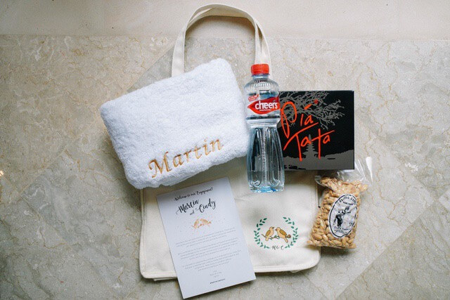 White towel, water bottle, packet of peanuts and some literature with a carry bag